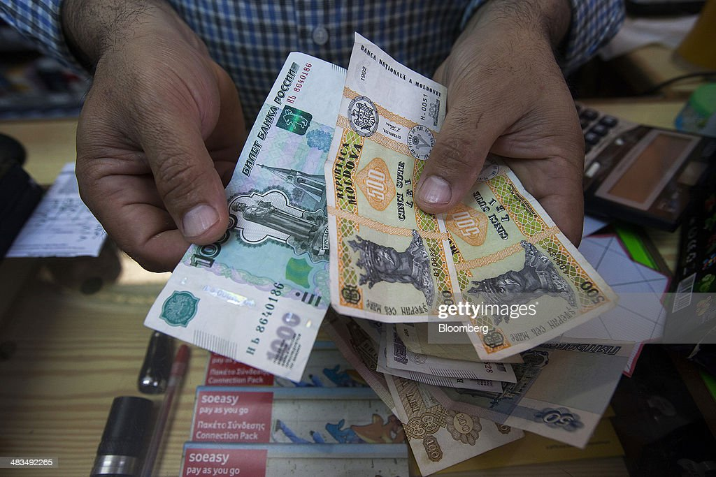 An employee displays Russian ruble banknotes, left, and Moldovan leu banknotes, right, in this arranged photograph at a currency exchange in Limassol, Cyprus, on Tuesday, April 8, 2014. Cyprus wants to shield financial flows with Russia, where it's the biggest foreign investor, as the U.S. and the European Union ratchet up sanctions in response to President Vladimir Putin's annexing Crimea from Ukraine. Photographer: Andrew Caballero-Reynolds/Bloomberg via Getty Images
