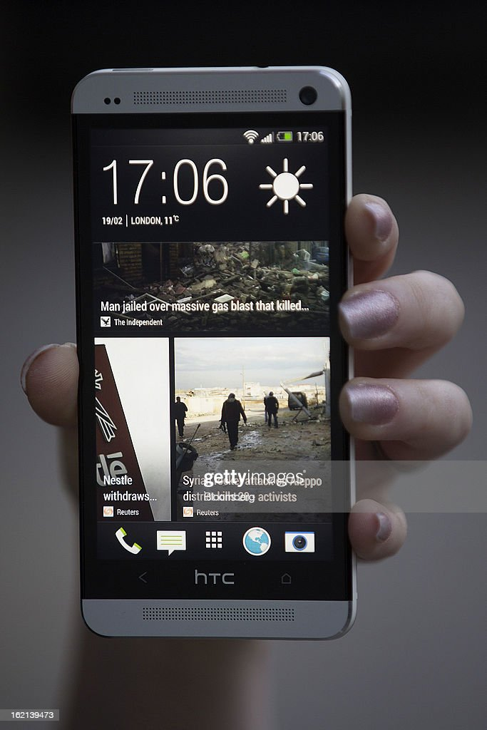 An employee displays the new HTC One smartphone for a photograph during a launch event in London, U.K., on Tuesday, Feb. 19, 2013. HTC Corp. introduced its new flagship HTC One smartphone at a launch event in London today. Photographer: Simon Dawson/Bloomberg via Getty Images