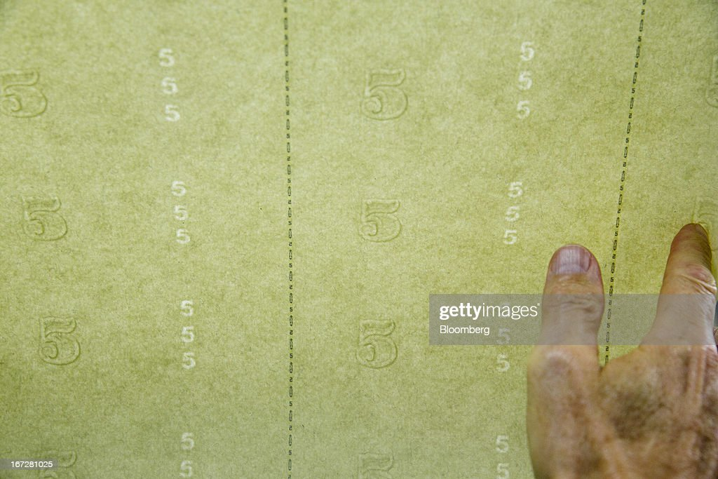 An employee displays the watermark on currency paper before being printed into five dollar notes at the Bureau of Engraving and Printing in Washington, D.C., U.S., on Tuesday, April 23, 2013. Stocks rallied amid growth in U.S. home sales, better-than-forecast earnings and speculation the European Central Bank will cut interest rates. U.S. equities recovered after briefly erasing gains following a false report of explosions at the White House. Photographer: Andrew Harrer/Bloomberg via Getty Images