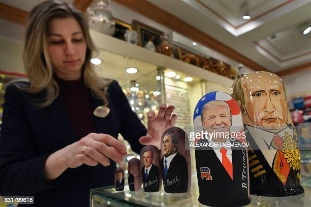 An employee displays traditional Russian wooden nesting dolls Matryoshka dolls depicting US Presidentelect Donald Trump Russian President Vladimir...