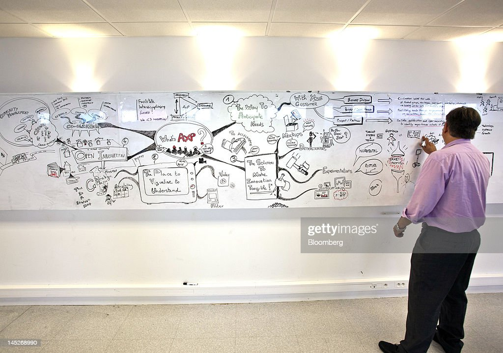 An employee draws on a message board inside the creative center at the