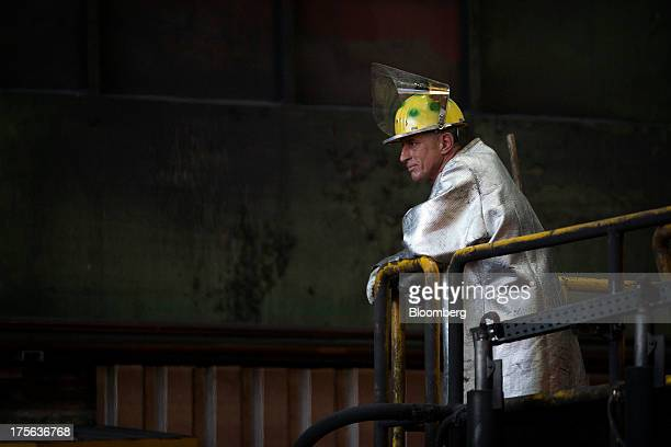 An employee dressed in heat retardant safety clothing takes a break outside the furnace shop at the Badische Stahlwerke GmbH steel mill in Kehl...