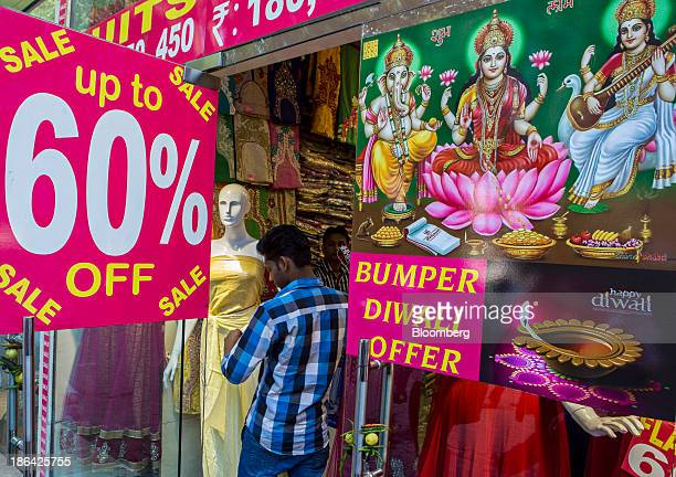 An employee dresses a mannequin in the window of a sari store displaying signage for Diwali sales in New Delhi India on Thursday Oct 31 2013 The...