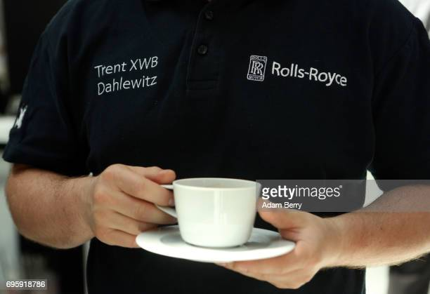 An employee drinks a cup of coffee on the assembly line for the RollsRoyce Trent XWB airplane engine to be used in the Airbus A350 XWB aircraft on...