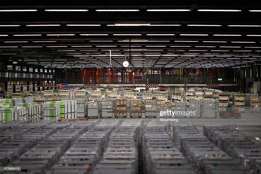 An employee drives a cart as he transports cages of flowers at FloraHolland, the largest flower auction in the world, in Aalsmeer, Netherlands, on Tuesday, March 11, 2014. The Netherlands' flower and plant exports, the world's biggest, fell 2.3 percent last year as declining consumer purchasing power was compounded by cold spring weather in Europe and a summer heat wave that hurt sales. Photographer: Jasper Juinen/Bloomberg via Getty Images