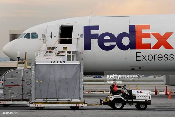 An employee drives a container past a cargo plane at the FedEx Corp distribution hub at Los Angeles International Airport in Los Angeles California...