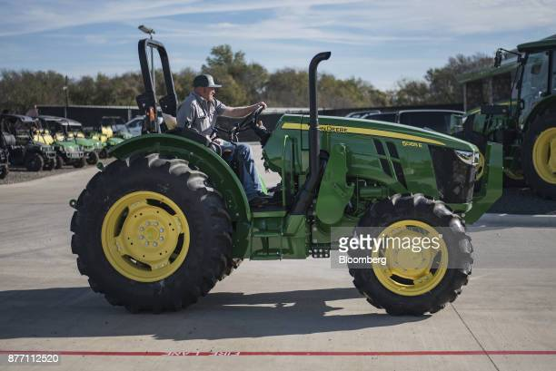 An employee drives a Deere Co John Deere 5085 E tractor at a United Ag Turf dealership in Waco Texas US on Monday Nov 20 2017 Deere Co is scheduled...