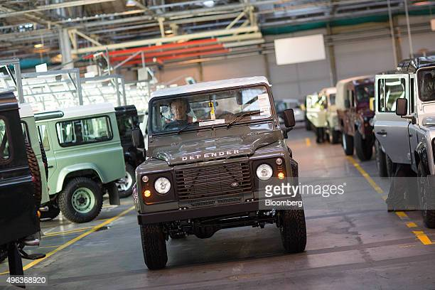 An employee drives a Land Rover Defender automobile off the inspection line at Tata Motors Ltd's Jaguar Land Rover vehicle manufacturing plant in...