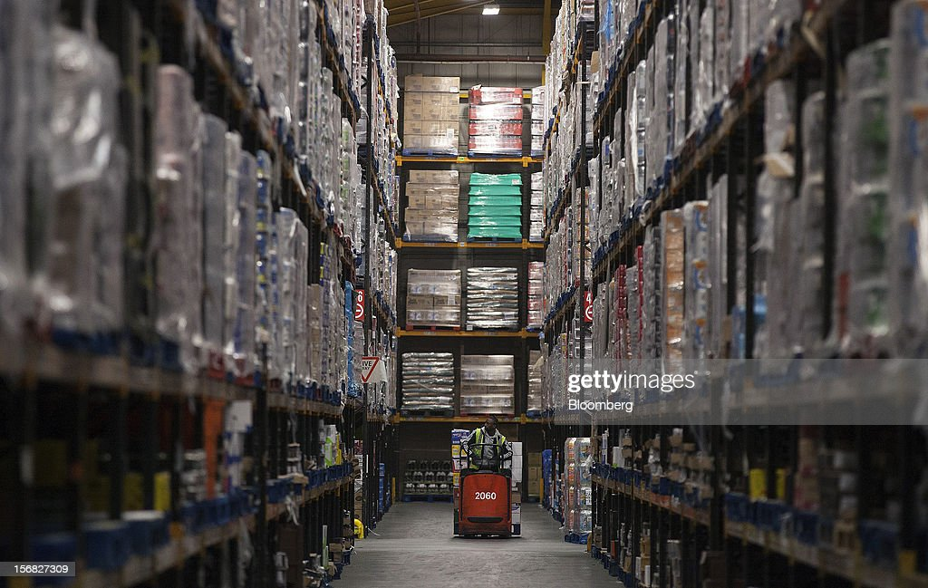An employee drives a Linde AG pallet truck down a storage aisle at WM Morrison Supermarkets Plc's distribution center in Wakefield, U.K., on Thursday, Nov. 22, 2012. Britain's economy will return to growth next year after stagnating in 2012, with expansion weighted in the second half, according to Bank of England projections published yesterday. Photographer: Simon Dawson/Bloomberg via Getty Images