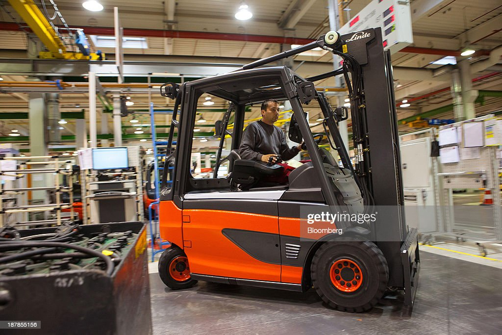 An employee drives a Linde E25 electric forklift truck on the vehicle production line at the Linde Material Handling GmbH factory, a unit of Kion Group AG, in Aschaffenburg, Germany, on Tuesday, Nov. 12, 2013. Kion Group AG, the German forklift-maker which listed shares in June, is looking to expand its global sales network via acquisitions to catch up with main competitor Toyota Industries Corp. Photographer: Krisztian Bocsi/Bloomberg via Getty Images