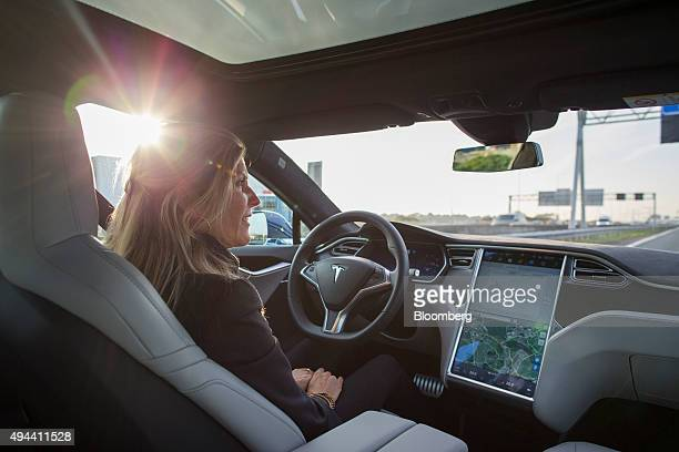 An employee drives a Tesla Motors Inc Model S electric automobile equipped with Autopilot hardware and software handsfree on a highway in Amsterdam...