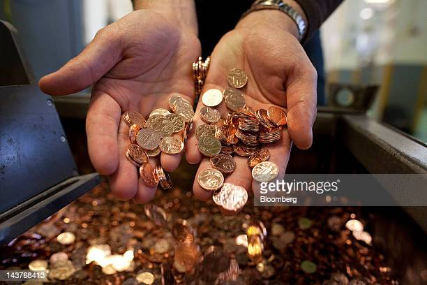 An employee drops newlyminted 2 cent euro coins into a container in this arranged photograph at the Bank of Greece's Printing Works Department and...