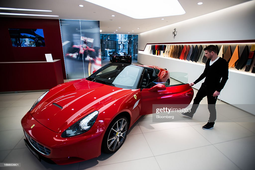An employee examines a Ferrari California sports car in the showroom of an automobile dealership in Budapest, Hungary, on Wednesday, May 15, 2013. Ferrari SpA, the Italian supercar manufacturer owned by Fiat SpA, plans to reduce sales to fewer than 7,000 vehicles this year to 'maintain the exclusivity' of the brand. Photographer: Akos Stiller/Bloomberg via Getty Images