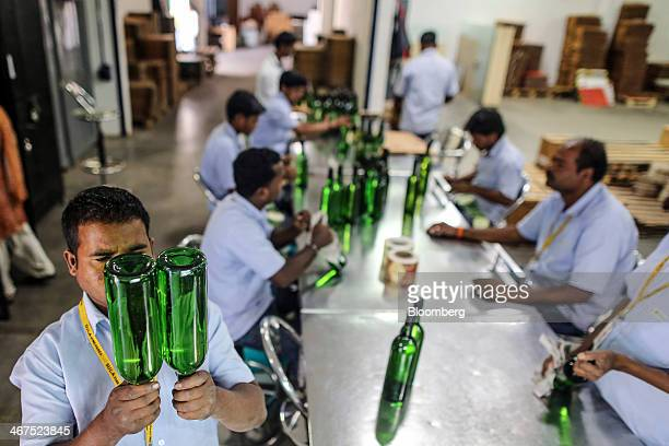 An employee examines bottles of Sula Samara White wine in the labeling department at Sula Vineyards' production facility operated by Nashik Vintners...