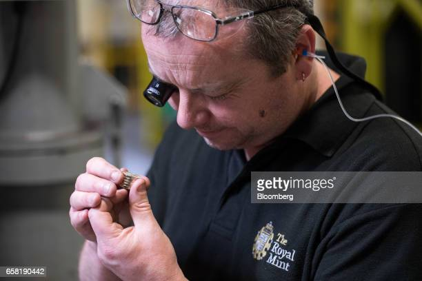 An employee examines new British one pound coins during production at The Royal Mint in Llantrisant UK on Thursday March 23 2017 Britain's Royal Mint...