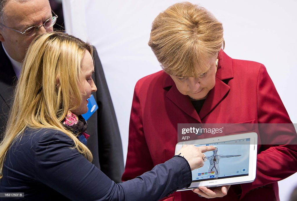 An employee explains German Chancellor Angela Merkel (R) a tablet device at the booth of Samsung Electronics during the opening event of the world's largest computer expo CeBIT high-tech fair on March 5, 2013 in Hanover, central Germany. Poland is this year's partner country of the fair running from March 5 to 9, 2013.