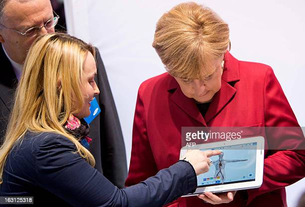 An employee explains German Chancellor Angela Merkel a tablet device at the booth of Samsung Electronics during the opening event of the world's...