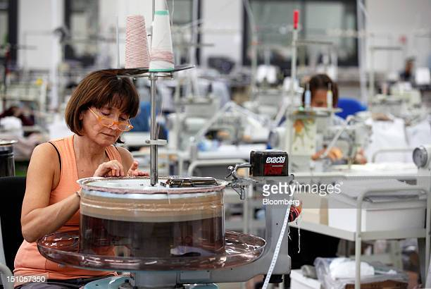 An employee feeds cashmere threads into a sewing machine during the manufacturing stages of garment production at Brunello Cucinelli SpA's facility...
