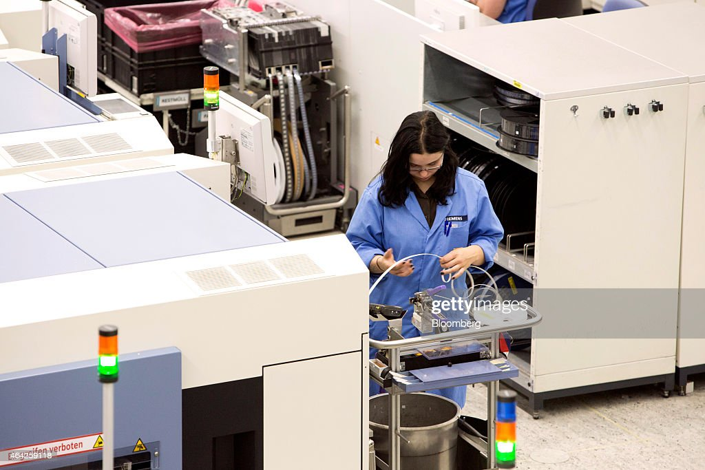 An employee feeds material into a machine on the surfacemount technology electronic circuit automated assembly line at the Siemens AG electronics...