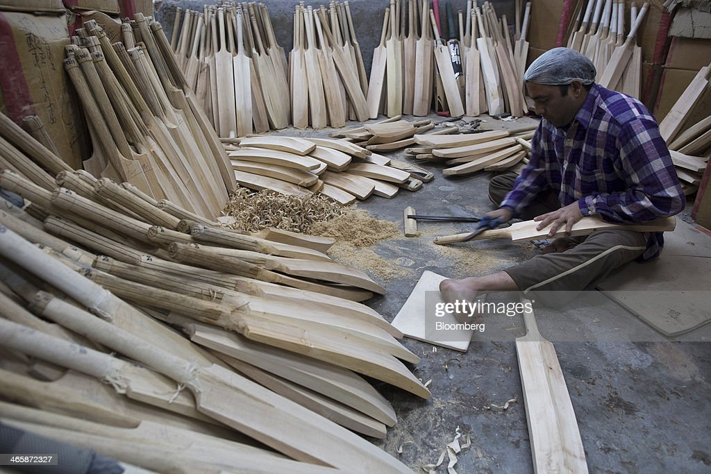 An employee files a cricket bat handle at a Stanford Cricket Industries factory in Meerut, Uttar Pradesh, India, on Wednesday, Jan. 29, 2014. The Indian Premier League (IPL), the worlds richest cricket competition, auction for IPL 2014 is scheduled to begin on Feb. 12 with the seasons first match to be played on April 8. Photographer: Prashanth Vishwanathan/Bloomberg via Getty Images