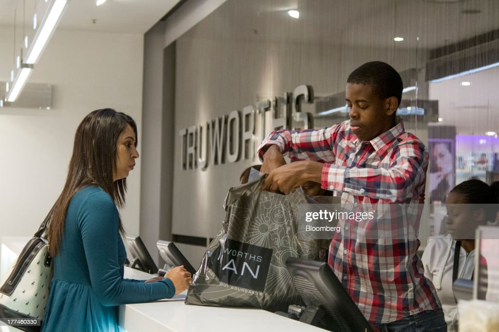 An employee fills a bag with a customer's purchases at the cash desk inside a Truworths International Ltd. Man retail store in the Sandton district of Johannesburg, South Africa, on Thursday, Aug. 22, 2013. Massmart Holdings Ltd., the South African food and goods wholesaler owned by Wal-Mart Stores Inc., said revenue growth continued to slow in August after a downturn in consumer spending hurt first-half earnings. Photographer: Nadine Hutton/Bloomberg via Getty Images