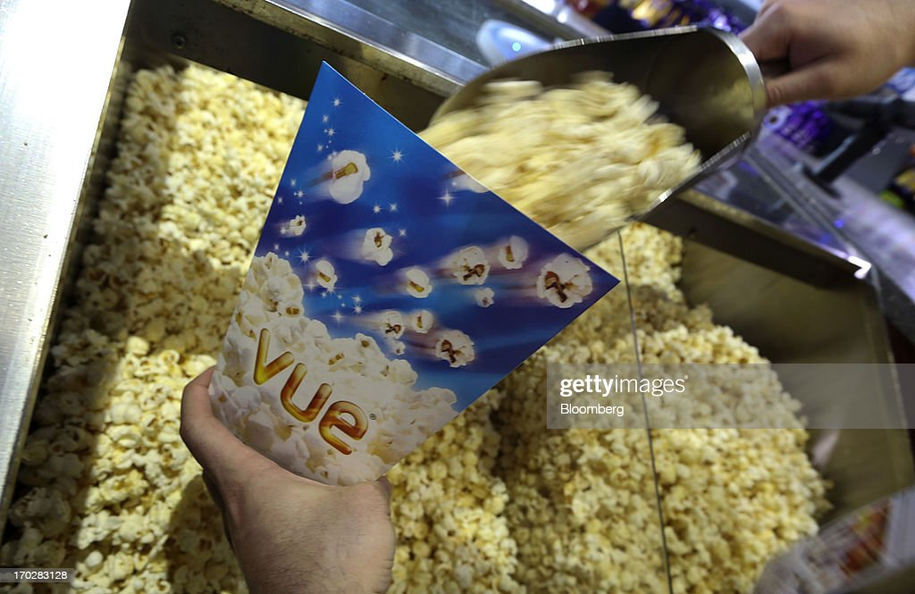 An employee fills a carton with popcorn in this arranged photograph at a Vue Cinema, operated by Vue Entertainment Ltd., at the Westfield Stratford City retail complex in London, U.K., on Tuesday, June 4, 2013. Vue Entertainment, the U.K. cinema chain bought by private equity firm Doughty Hanson & Co., are continuing to expand in Europe, recently acquiring Poland's second-largest cinema chain Multikino. Photographer: Chris Ratcliffe/Bloomberg via Getty Images