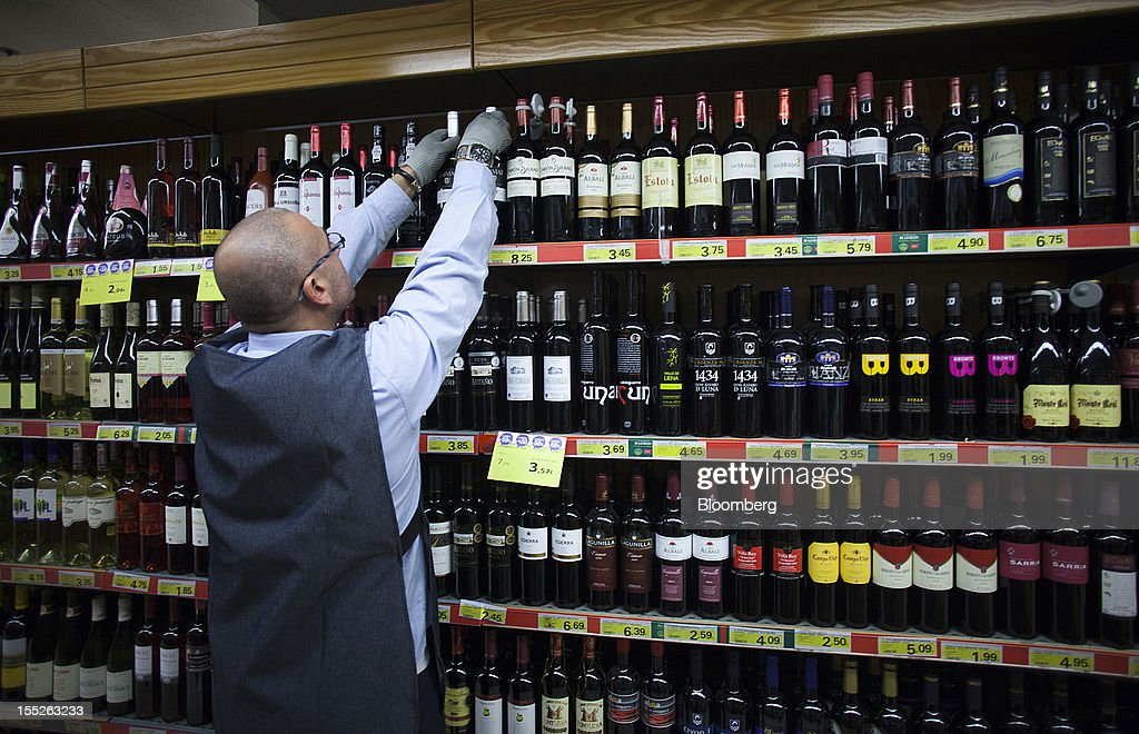 An employee fills a shelf with bottles of Spanish red wine at an Eroski Group supermarket in Madrid, Spain, on Friday, Nov. 2, 2012. Spain is unlikely to need a full bailout while any request from the euro area's fourth-largest economy for alternative support measures must be met with a swift response, Finnish Prime Minister Jyrki Katainen said. Photographer: Angel Navarrete/Bloomberg via Getty Images