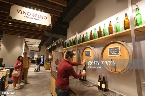 An employee fills a wine bottle from a barrel tap inside the new Eataly food store operated by Eataly Net Srl at the Kievsky shopping mall in Moscow...