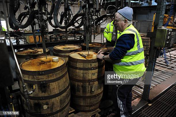 An employee fills American oak barrels with Jameson whiskey produced by Irish Distillers Ltd at the PernodRicard SA distillery in Middleton Ireland...