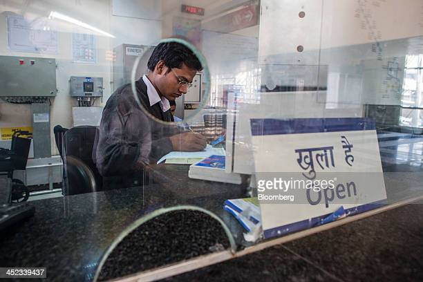 An employee fills in paperwork behind a ticket counter at Sikanderpur Station operated by Rapid MetroRail Gurgaon Ltd in Gurgaon Haryana India on...