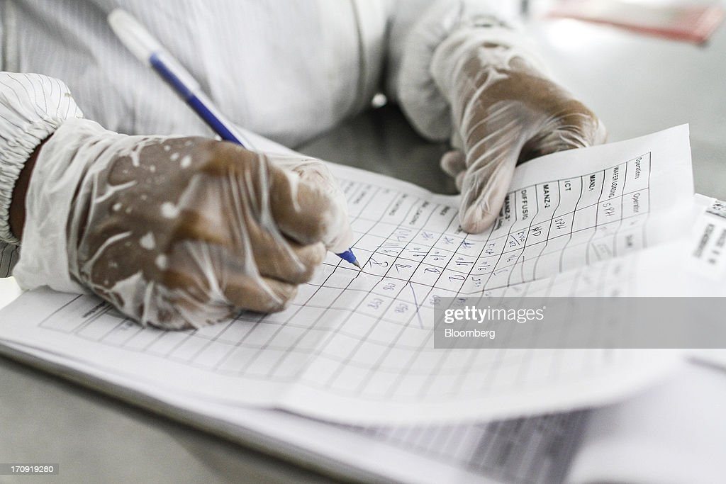 An employee fills in paperwork on the solar cell production line at the Tata Power Solar Systems Ltd. manufacturing plant in Bangalore, India, on Tuesday, June 11, 2013. Tata Groups solar unit is expanding its business building plants for customers, forecasting that offices and factories will be paying more for grid power than solar by 2016 in most Indian states. Photographer: Dhiraj Singh/Bloomberg via Getty Images