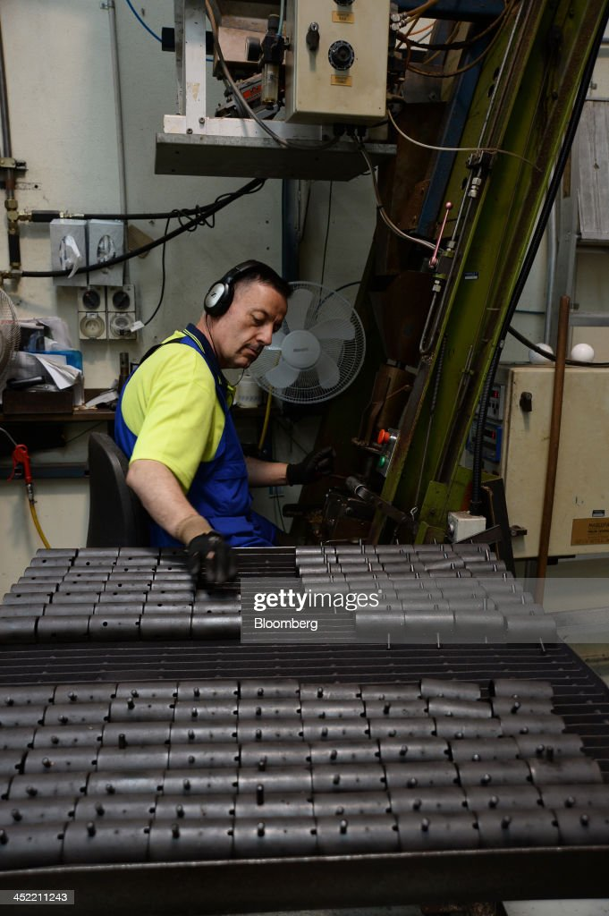An employee fills molds for making the cork-and-rubber core of cricket balls at the Kookaburra Sports Pty Ltd. plant in Melbourne, Australia, on Tuesday, Nov. 26, 2013. Australian businesses need to boost efficiency to maintain growth in living standards, Reserve Bank of Australia Deputy Governor Philip Lowe said. Photographer: Carla Gottgens/Bloomberg via Getty Images