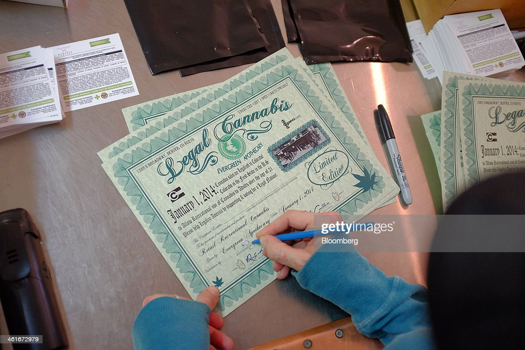An employee fills out a certificate they give to customers commemorating the sale of legal cannabis inside the Evergreen Apothecary in Denver, Colorado, U.S., on Thursday, Jan. 9, 2014. Colorado has just legalized the commercial production, sale, and recreational use of marijuana, while Washington State will begin its own pot liberalization initiative at the end of February. On Jan. 8, New York Governor Andrew Cuomo said his state would join 20 others and the District of Columbia in allowing the drug for medical purposes. Photographer: Matthew Staver/Bloomberg via Getty Images