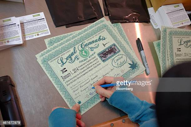 An employee fills out a certificate they give to customers commemorating the sale of legal cannabis inside the Evergreen Apothecary in Denver...