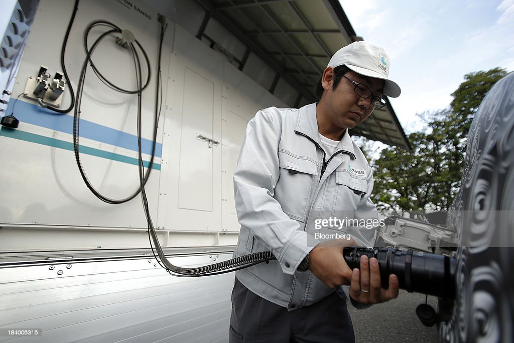 An employee fills up a Toyota Motor Corp. fuel cell vehicle (FCV) prototype, right, with hydrogen from Taiyo Nippon Sanso Corp.'s Hydro Shuttle hydrogen station during a demonstration at a media briefing on Toyota Motor Corp.'s advanced technologies in Tokyo, Japan, on Thursday, Oct. 10, 2013. Toyota has long held out hydrogen as the ultimate alternative to gasoline for powering autos. Soon, consumers will be able to kick the tires of its fuel cell-powered car and those of other automakers. Photographer: Kiyoshi Ota/Bloomberg via Getty Images