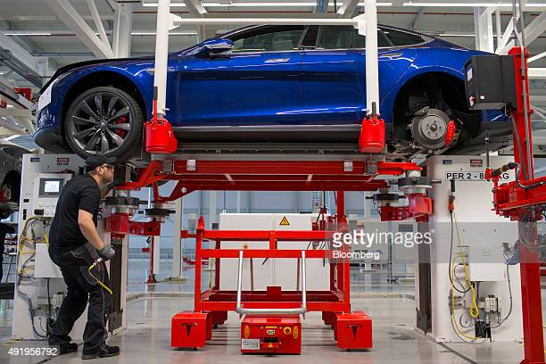 An employee fits a battery pack under a Tesla Model S automobile on the final assembly at the Tesla Motors Inc factory in Tilburg Netherlands on...
