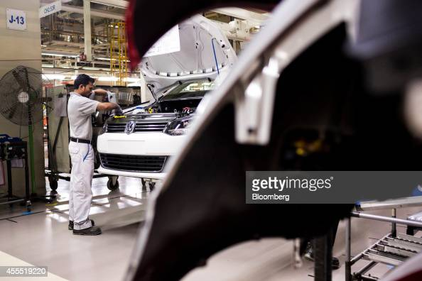 An employee fits a headlight to a Volkswagen AG Vento automobile on the production line at the Volkswagen India Pvt plant in Chakan Maharashtra India...