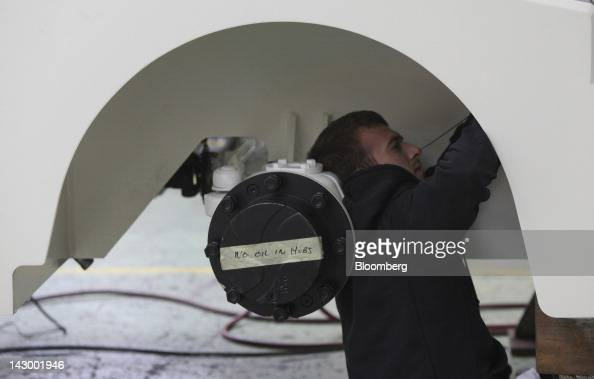 An employee fits a part inside the wheelarch of an aviation towing tractor at the Douglas Equipment plant owned by CurtissWright Corp in Cheltenham...