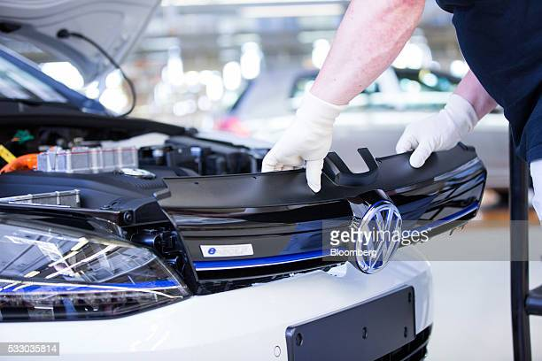 An employee fits the front grill to a Volkswagen eGolf electric automobile on the assembly line inside the Volkswagen AG factory in Wolfsburg Germany...