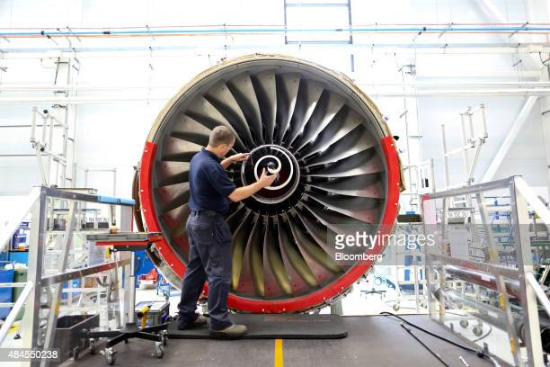 An employee fits the nose cone to a Trent 700 aircraft engine on the production line at the RollsRoyce Holdings Plc factory in Derby UK on Wednesday...