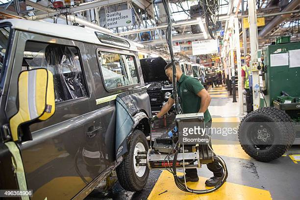 An employee fits wheel nuts onto the tyre of a Land Rover Defender automobile at Tata Motors Ltd's Jaguar Land Rover vehicle manufacturing plant in...