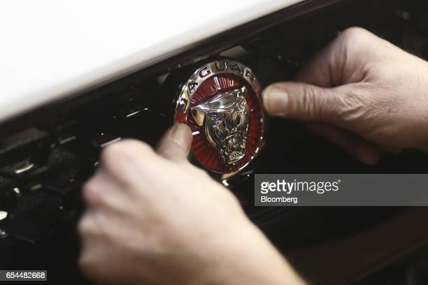 An employee fixes a badge to the front grille of a Jaguar Ftype automobile as it moves through the final inspection area at Tata Motors Ltd's Jaguar...