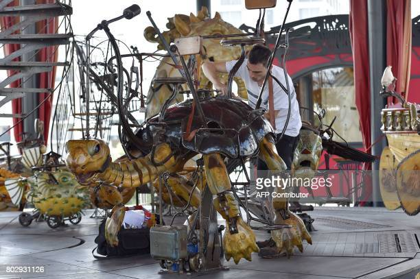 An employee fixes a mechanical turtle made of wood and steel in the 'Carrousel des Mondes Marins' of 'Les Machines de L'Ile' in Nantes western France...