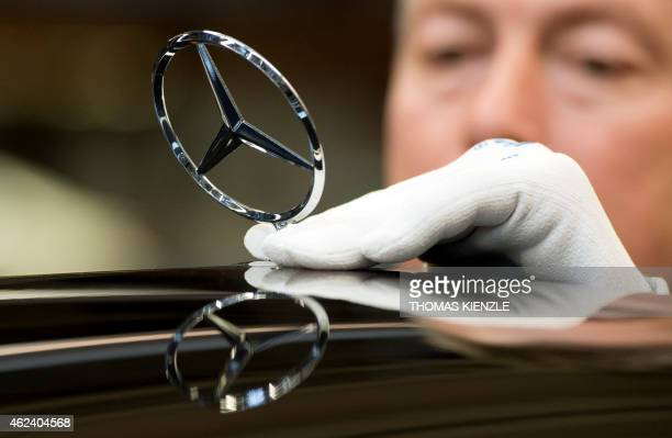 An employee fixes a Mercedes star to the front lid of a MercedesBenz SClass car on the assembly line of the Daimler factory in Sindelfingen...