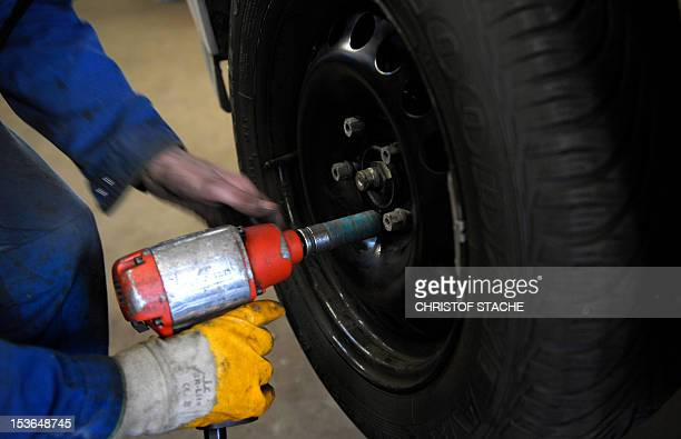 An employee fixes a winter tyre on a car in a small garage in Ingolstadt southern Germany on November 26 2010 The upper house of parliament decided...