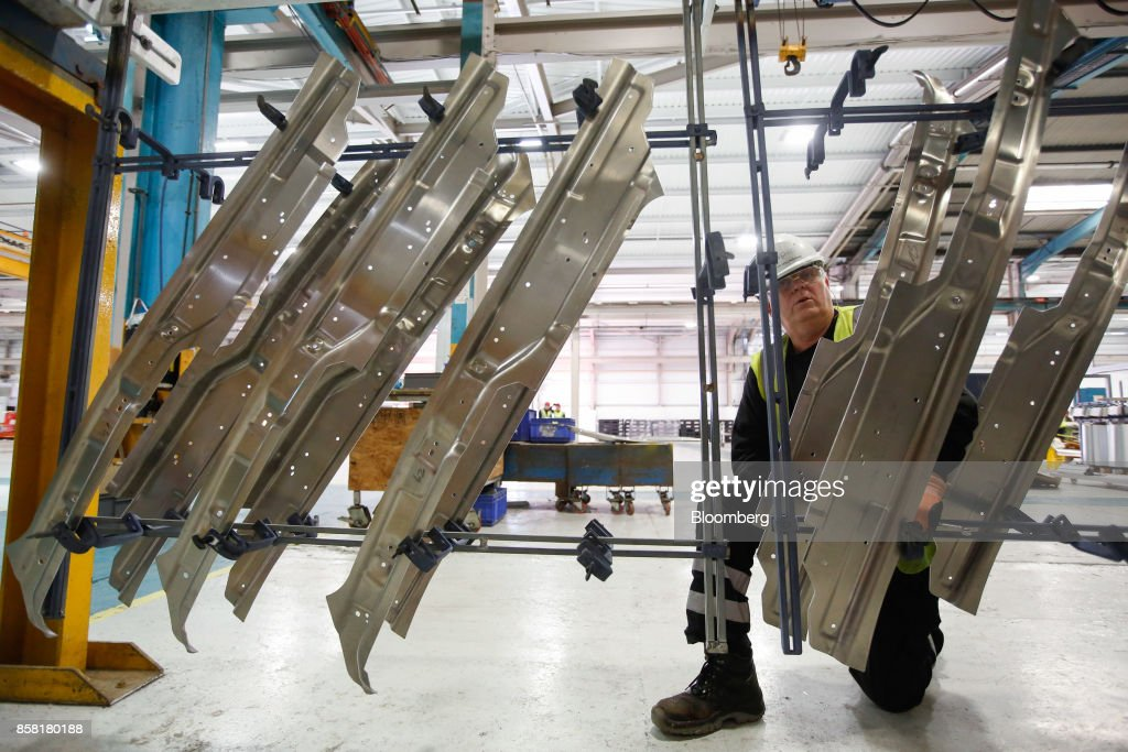An employee fixes aluminum parts to a flight bar to be dipped into cleaning and anodising tanks at the Sapa SA aluminum plant in Bedwas, U.K., on Wednesday, Oct. 4, 2017. After being closed for three years due to a weak market,Sapa's aluminum plant in south Wales reopened to supply lightweight parts for automakers such as London Electric Vehicle Co., the maker of black cabs. Photographer: Luke MacGregor/Bloomberg via Getty Images