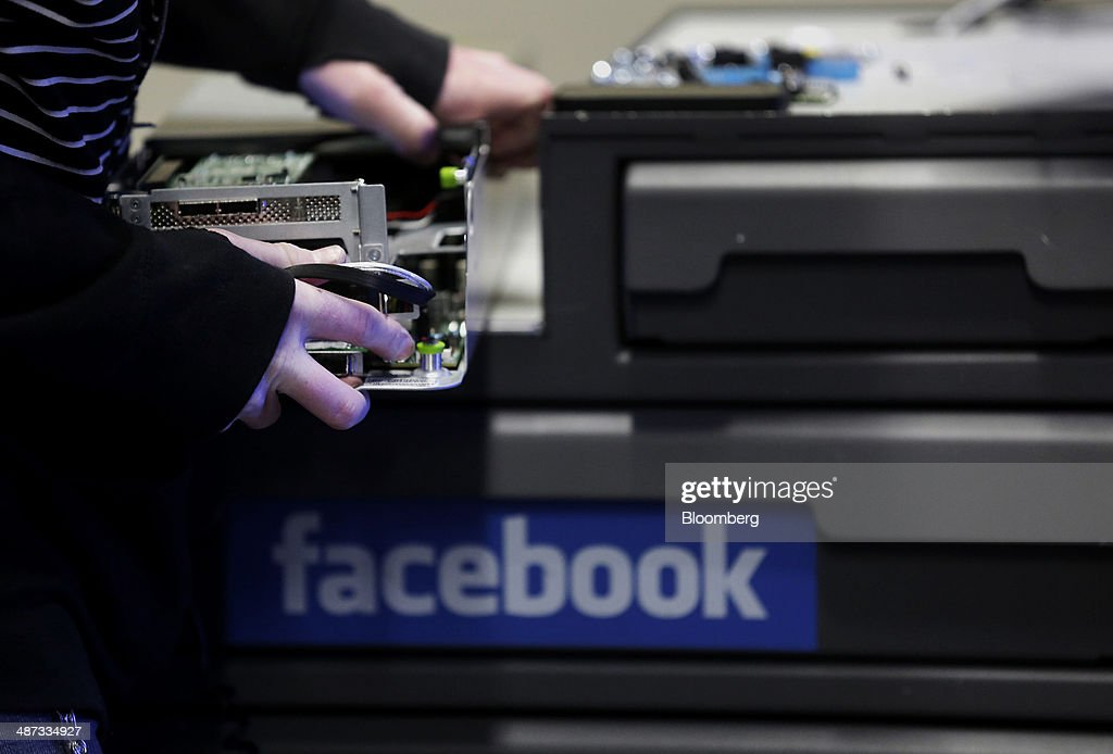 An employee fixes part of a web server inside the Facebook Inc. Prineville Data Center in Prineville, Oregon, U.S., on Monday, April 28, 2014. The Facebook Prineville Data Center features leading energy-efficient technology, including features such as rainwater reclamation, a solar energy installation for providing electricity to the office areas and reuse of heat created by the servers to heat office space. Photographer: Meg Roussos/Bloomberg via Getty Images