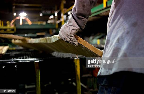 An employee flips a board on a conveyor belt during production at the Nicolet Hardwoods Corp lumber mill in Laona Wisconsin US on Wednesday Oct 10...