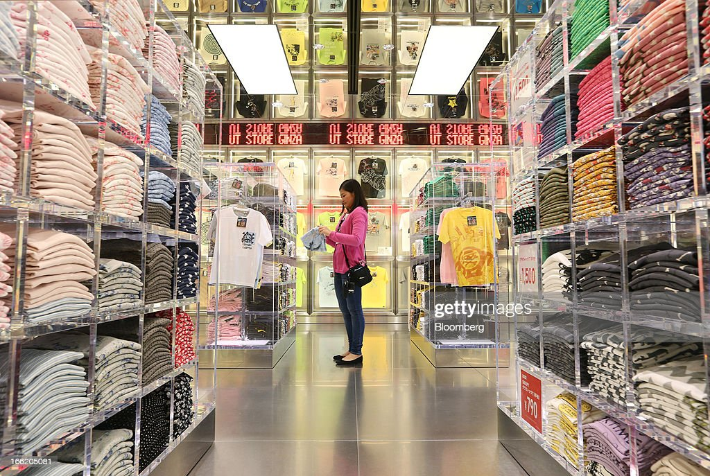 An employee folds a shirt displayed at Fast Retailing Co.'s Uniqlo store in the Ginza district of Tokyo, Japan, on Wednesday, April 10, 2013. Fast Retailing, Asia's largest apparel retailer, is scheduled to announce earnings tomorrow. Photographer: Yuriko Nakao/Bloomberg via Getty Images