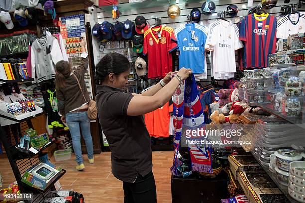 An employee folds an Atletico de Madrid scarf in a shop a day before the UEFA Champions league Final of Real Madrid against Atletico de Madrid on May...